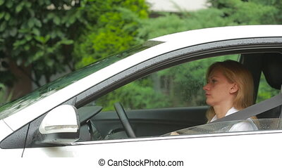 woman get into the car in the rain wear seat belts - woman...