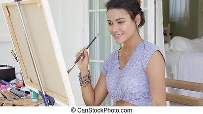 Attractive female artist working on a canvas concentrating...