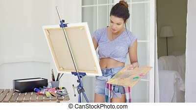 Artistic young woman working on a painting on an outdoor...