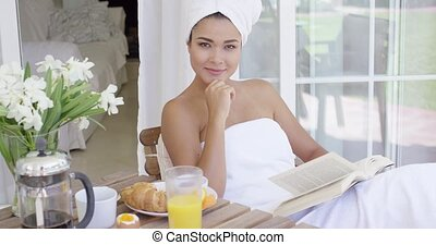 Gorgeous young woman relaxing with a book as she enjoys her...