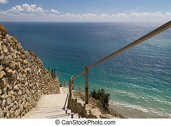 Stone stairs down to azure sea. Steep descent. Rock wall. Blue sparkling water.