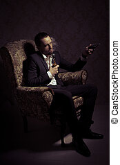 Young handsome man sitting in chair, holding gun and smoking pipe over vintage background