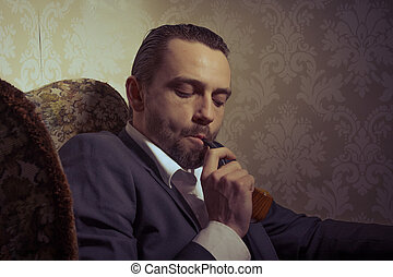 Young handsome man sitting in chair and smoking pipe over vintage background