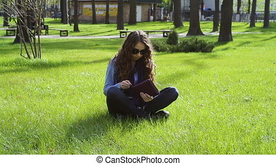 beautiful young woman sitting in the park on the grass and...