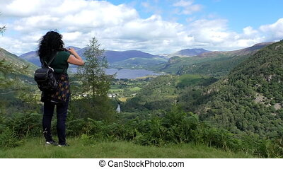 Woman taking mountain view picture