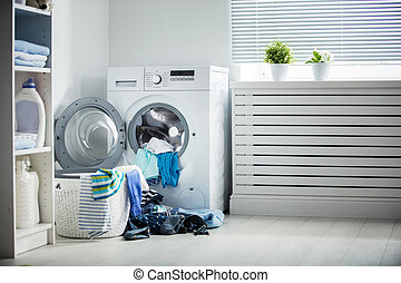 laundry. A washing machine and a pile of dirty clothes at...