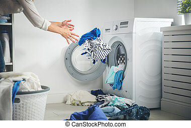 laundry concept. dirty clothes flies into washing machine -...