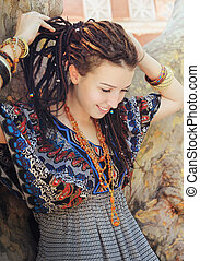 Young smiling woman portrait with dreadlocks dressed in boho style ornamental dress