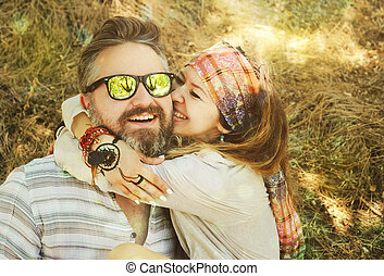 Indie style smiling couple, woman embracing man, hipster outfit, boho chic