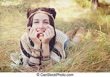 Boho style smiling woman portrait, girl have a fun lying outdoor in autumn sunny park