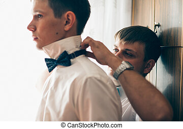 friend of the bridegroom helps him to wear a bow tie