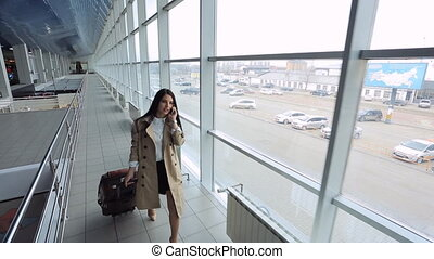 Up view of young female going down airport hall. Fashionable...