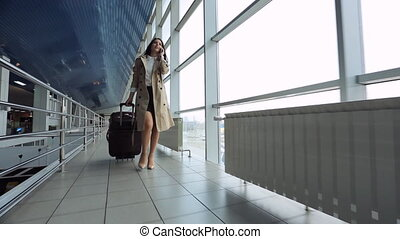 Young and beautiful woman is walking airport hall....