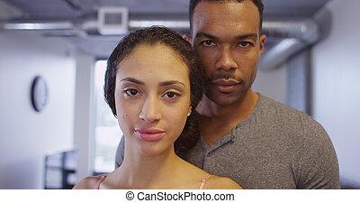 Close up of Black and Hispanic couple looking at camera...