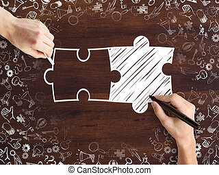 Business partnership - Male hands drawing puzzle pieces and...