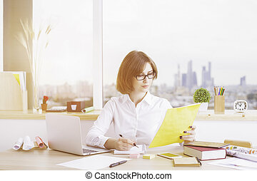 Attractive female doing paperwork at messy office desktop...