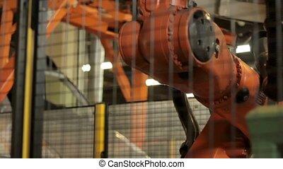 View of robot preparing to work on factory - Orange metallic...