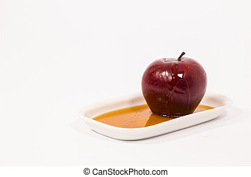 Red apple with drops of honey on white plate with honey...