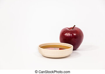 Red apple and bowl of honey isolated on a white background....