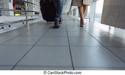Down view of couple walking down airport hall. Trying to...