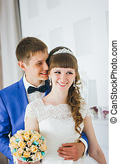 young groom kissing the bride in a studio interior.