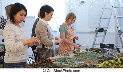 Women are working with flowers creating floristic...