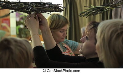 Women are making handmade decoration with flowers. Hanging...