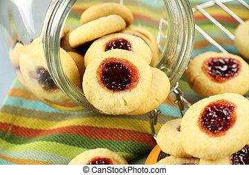 Jam Biscuits - Jam biscuits tumbled out of a glass jar with...