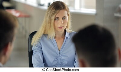 Woman is sitting in office having work interview or meeting.