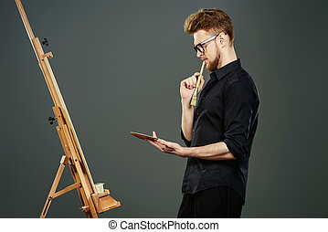 occupation - Male artist paints on an easel in the workshop....