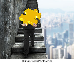 Businessman carrying gold puzzle piece climbing on old...