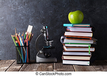 Notepads, supplies and apple in front of chalk board. Back...