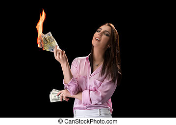 Concept of financial crisis. Woman burns money - Concept of...