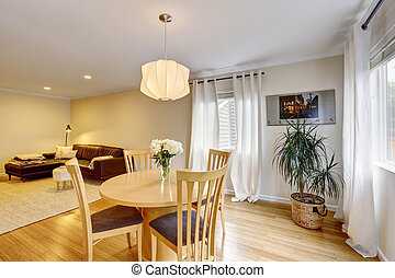 Cozy dining area with table set and curtains in creme tones.