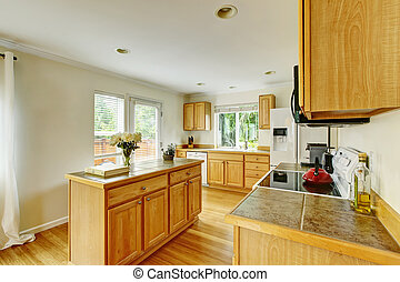 Kitchen room interior with wooden cabinets with marble tile counter top.