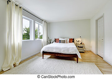 Bedroom interior in light tones with wooden bed and hardwood floor.