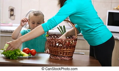 girl helps her mother pulling vegetables from the basket -...