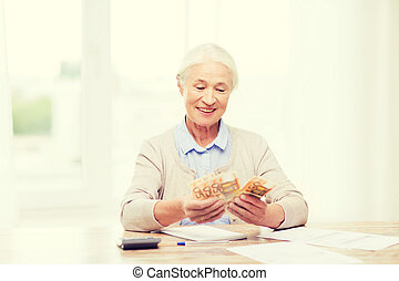 senior woman with money and papers at home - business,...