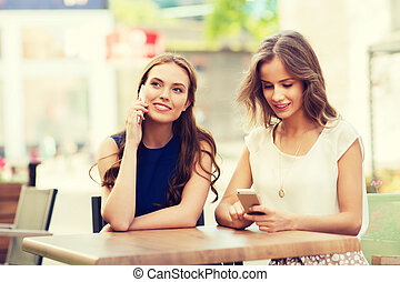 happy young women with smartphones at outdoor cafe -...