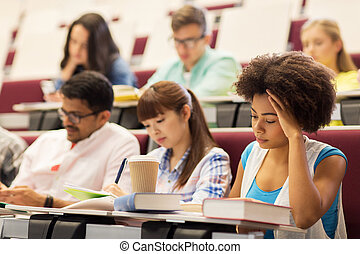 group of students with coffee writing on lecture -...