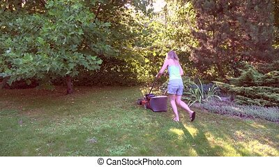 young woman work with grass cutter on own green garden 4K -...