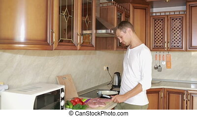 Man Beats Meat By Kitchen Hammer man preparing dinner - Man...
