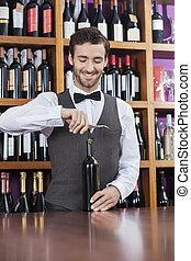 Bartender Using Corkscrew To Open Wine Bottle - Smiling...