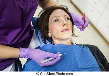 Dentist Examining Patient With Tools In Clinic - High angle...