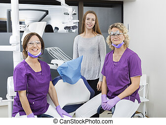 Female Dentists And Patient Smiling In Clinic - Portrait of...