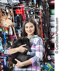 Smiling Woman Carrying French Bulldog At Pet Store -...