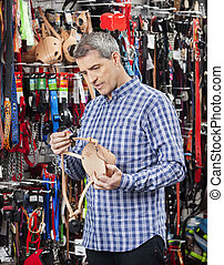 Customer Examining Dog Muzzle At Store - Mature male...