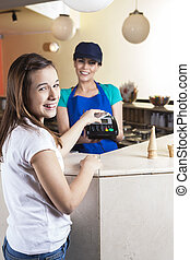 Happy Girl Making NFC Payment While Waitress Smiling -...