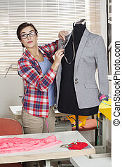 Confident Fashion Designer Pinning Suit On Mannequin