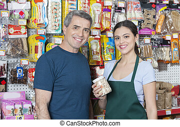 Saleswoman Holding Pet Food While Standing By Customer -...